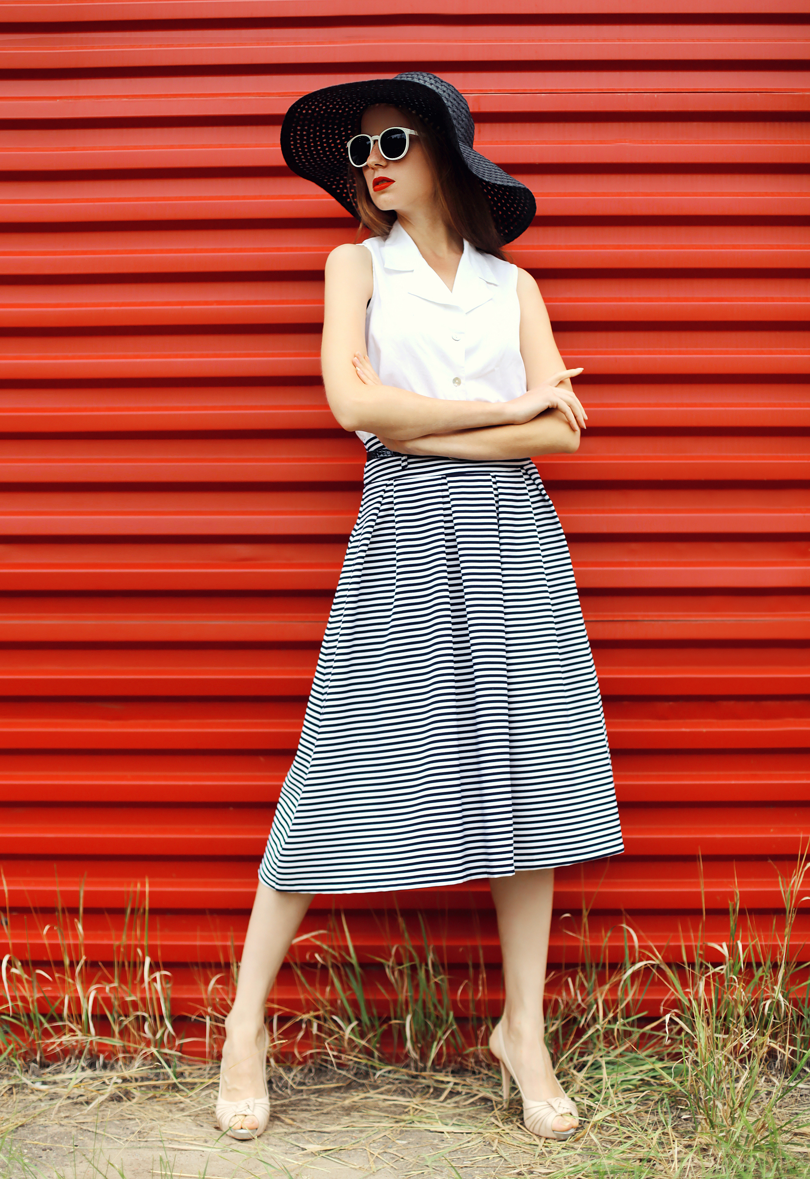 Fashion beautiful woman wearing a black straw hat, sunglasses and striped skirt over red background