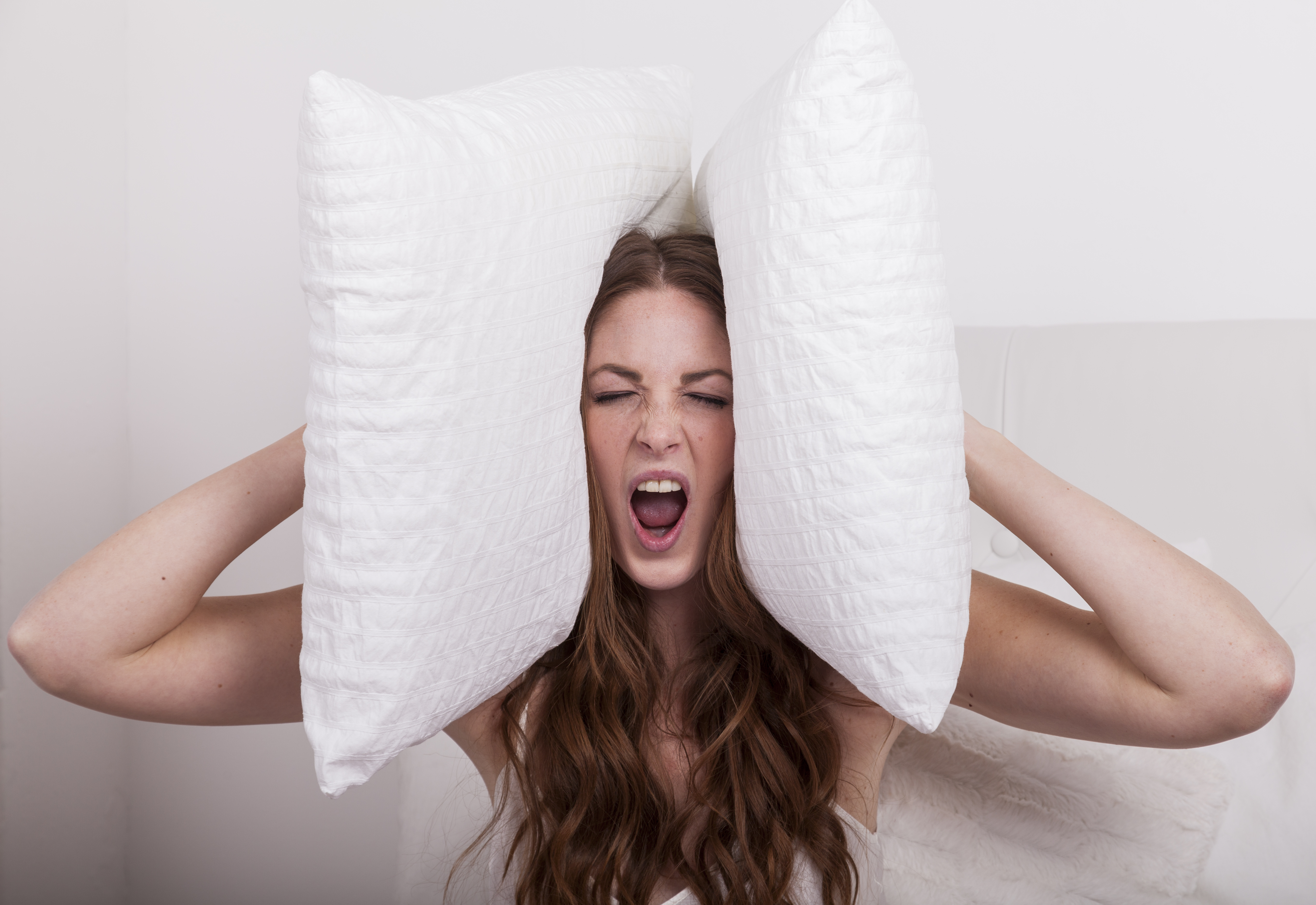 aggressive angry woman holds pillows to her ears due to extreme noise of the neighbours